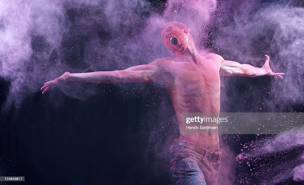 Young man in spray of colored powder : Stock Photo