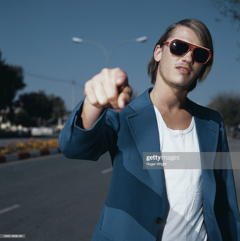 Young man in street wearing sunglasses, pointing, close-up