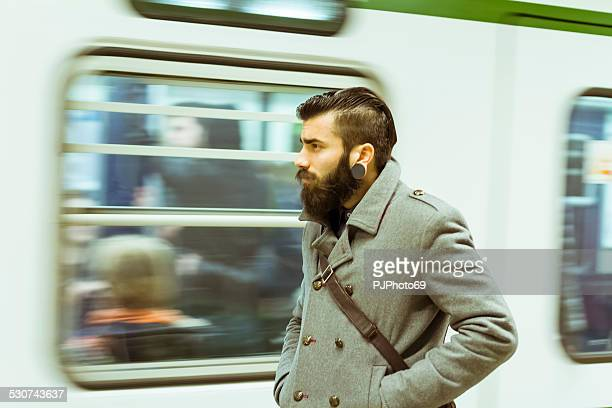 Young man (stylish hipster) in subway station
