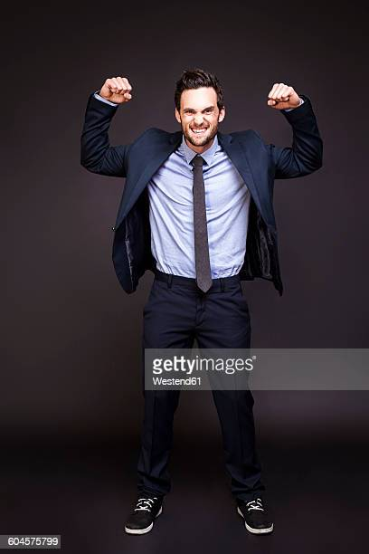 Young man in suit flexing his muscles