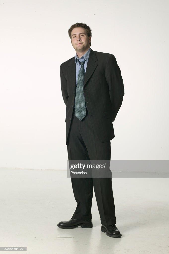 Young man in suit standing in studio, portrait : Stock Photo