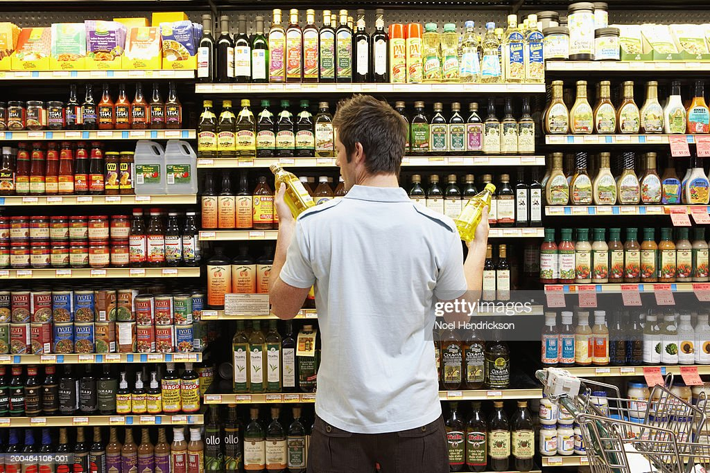 Young man in supermarket comparing bottles of oil, rear view, close-up : Stock Photo