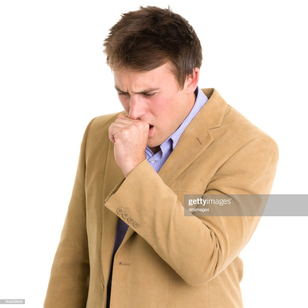 Young man in tan jacket coughing into his hand