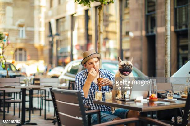 Young man in the city with his french bulldog