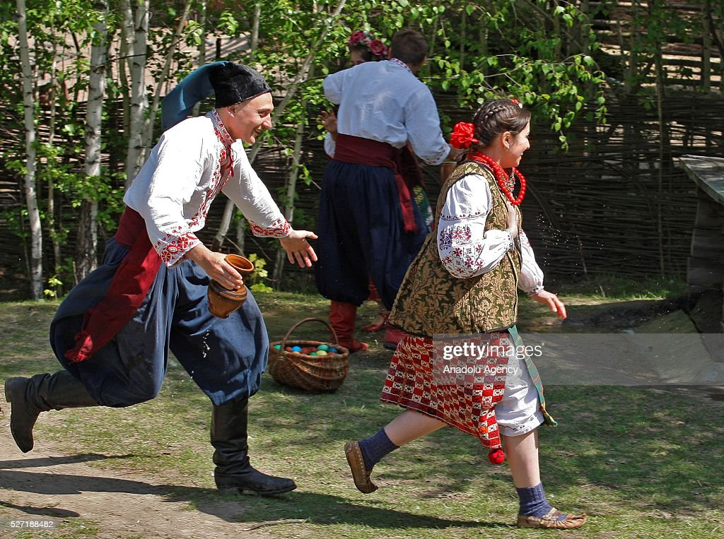 Young man in Ukrainian traditional clothe with a carafe of water in his hand running after a girl during folk Easter Tradition of pouring water called 'Pouring Monday' in open air Cossack village 'Mamaeva Sloboda', Ukraine,on May 02, 2016. The tradition of pouring water when single guys pour unmarried girls by water is celebrated on the first Monday after Orthodox Easter.