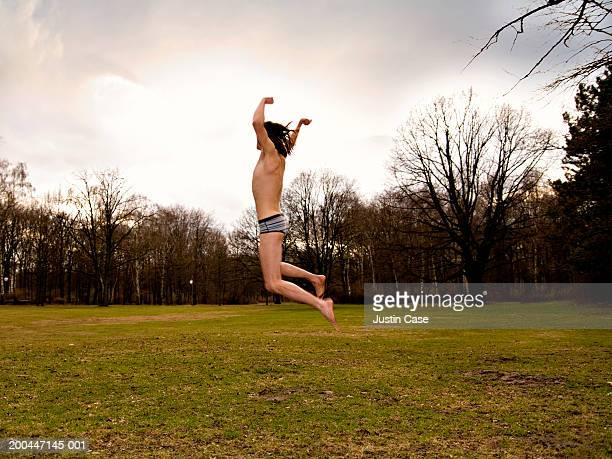 Young man in underwear jumping on grass, arms raised, side view