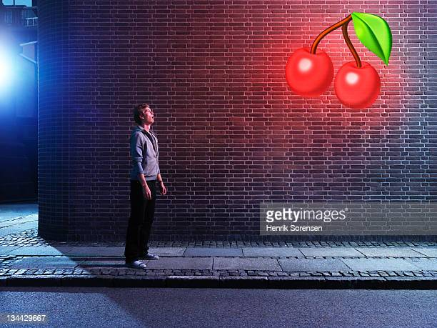 young man in urban environment looking at cherrys