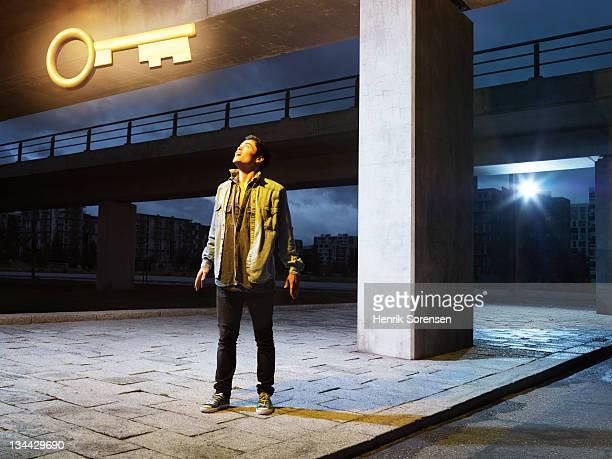 young man in urban environment looking at key
