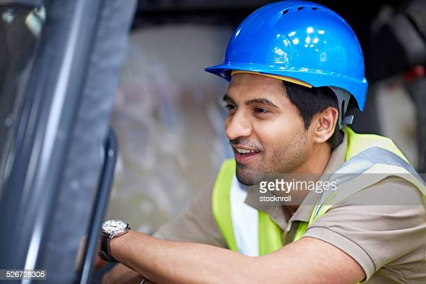 Young man in warehouse driving forklift truck