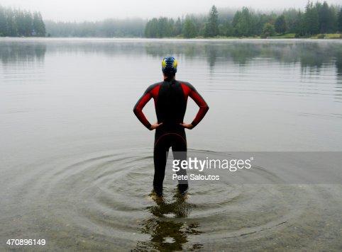 Young man in wet suit preparing to swim lake