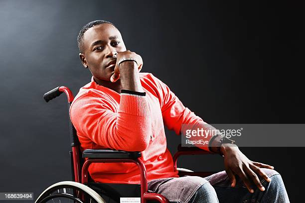 Young man in wheelchair is thoughtful, possibly depressed