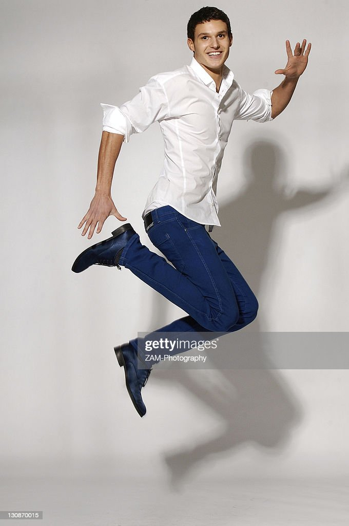 Young man in white shirt and blue jeans jumping stock for Man in white shirt