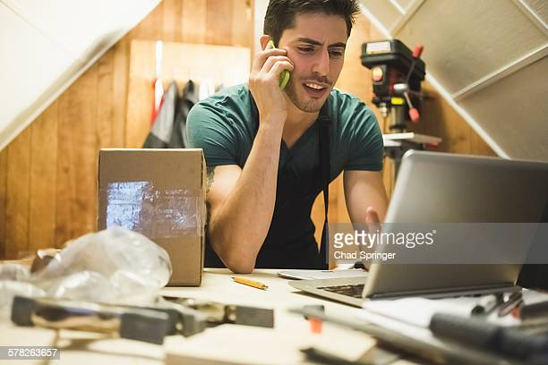 Young man in workshop sitting at desk talking on telephone looking at laptop