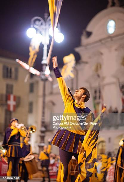 Young man in yellow costume throwing flag during Palio di Asti medieval festival, Asti, Piedmont, Italy