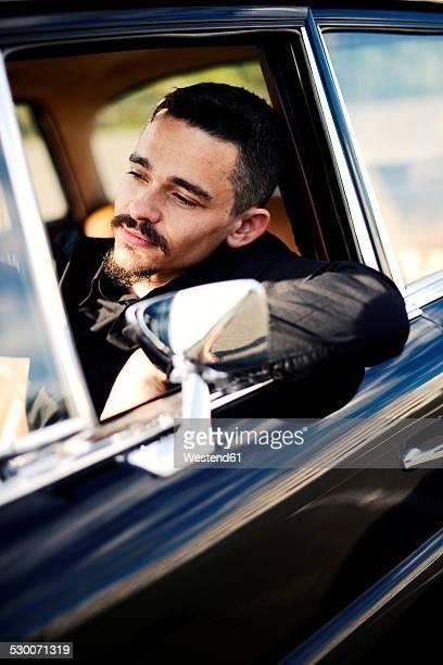 Young man inside vintage car