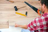 Young man installing laminate flooring in new apartment or house. High angle view. Home improvement and renovation concept