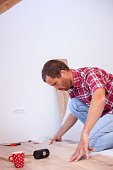 Young man installing laminate flooring in new apartment or house. Home improvement and renovation concept