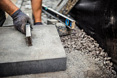Young man installing paving stones