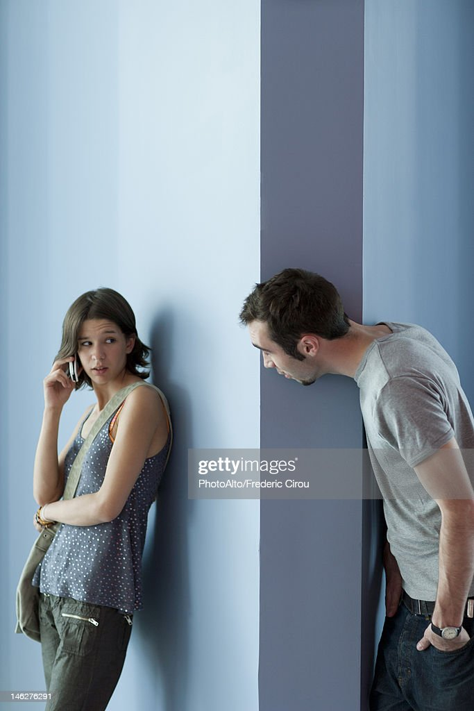 Young man interrupting young woman's cell phone call