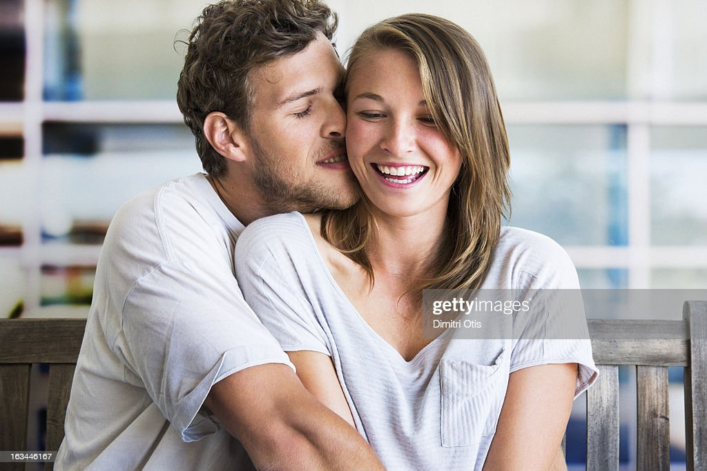 Young man intimately embracing laughing woman : Stock Photo
