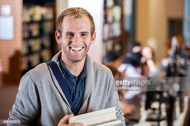 Hombre joven estudiante en la escuela moderna de la biblioteca