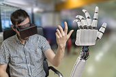 Young man is controlling robotic hand with virtual reality headset.