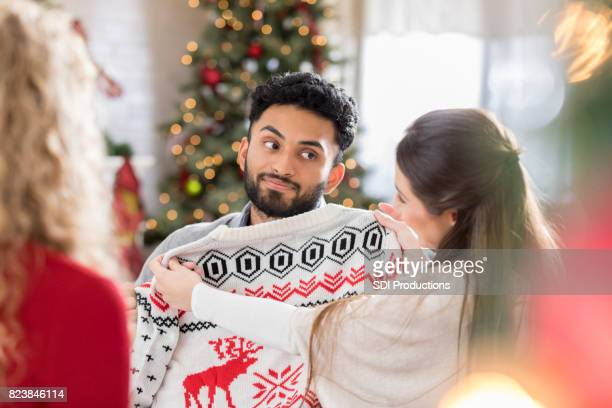 Young man is disappointed with new Christmas sweater