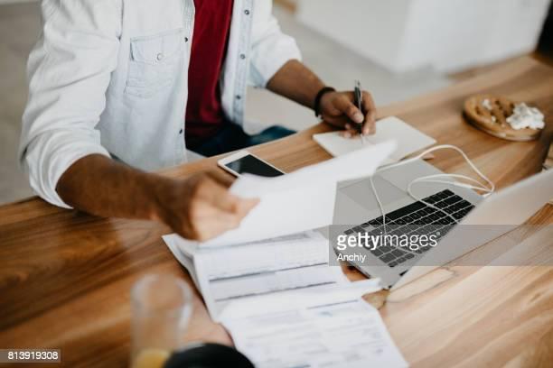 Junger Mann tut Finanzen zu Hause