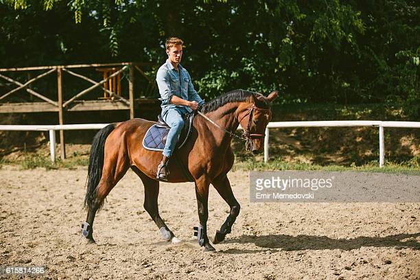 Young man is enjoying horseback riding in nature.