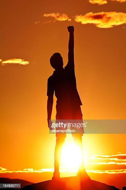 Junger Mann Faust in der Luft zu feiern, Sonnenuntergang Landschaft (I