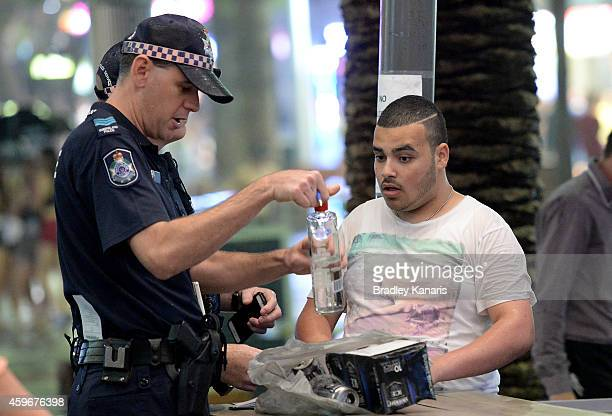 A young man is questioned and his bag searched by police during Australian 'schoolies' celebrations following the end of the year 12 exams on...