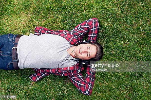 Young man is relaxing in the grass listening to music