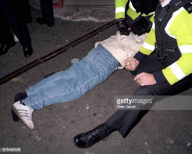A young man is restrained by police officers after they intervene to break up a fight outside a kebab shop on Union Street in Plymouth November 2001