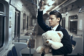 Young man is riding in an empty subway car. In his hands is a teddy bear