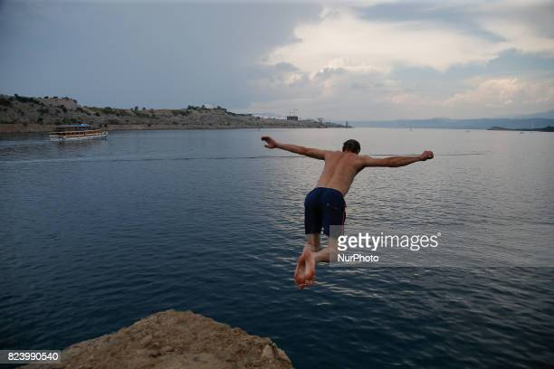 A young man is seen jumping off a cliff in Omisalj Croatia on 28 July 2017 In the background oil storage facilities owned by the JANAF oil...