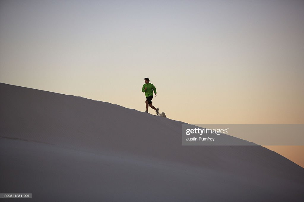 Young man jogging in desert, dusk : Stock Photo