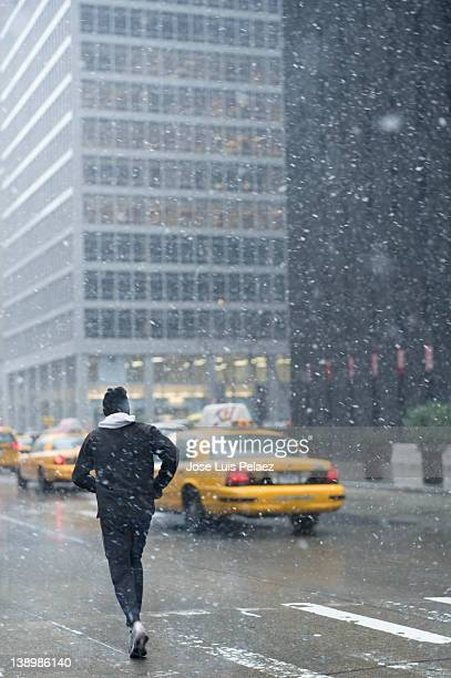 Young man jogging in the street during snow