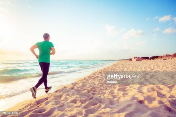 Jeune homme jogging sur la plage