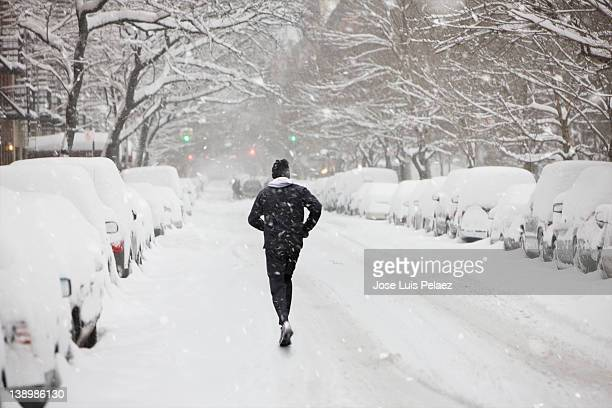 Young man jogging the street during snow
