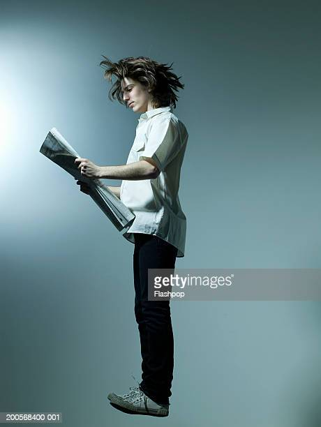Young man jumping and reading paper, side view