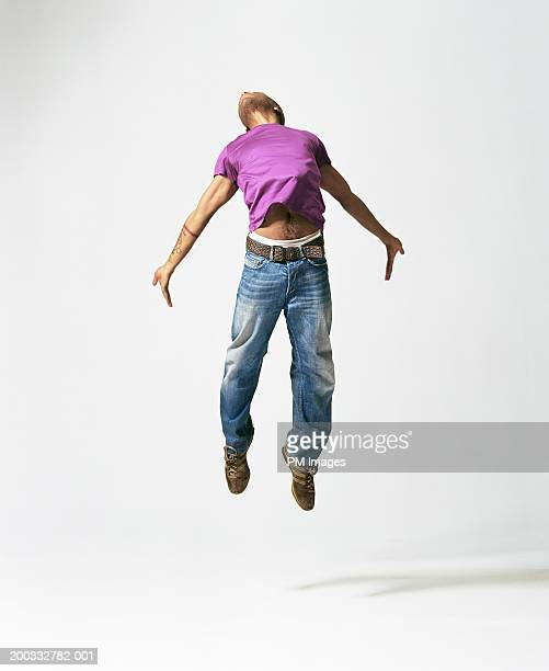 Young man jumping, arching back