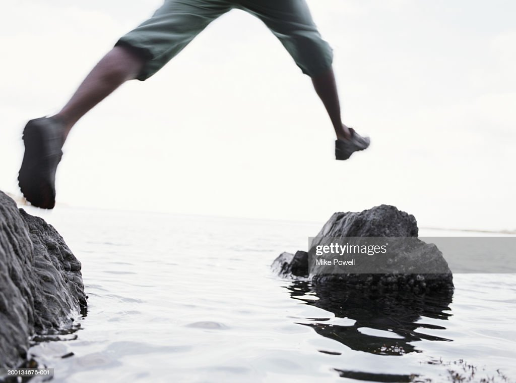 Young man jumping between rocks, low section (blurred motion) : Stock Photo