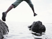 Young man jumping between rocks, low section (blurred motion)