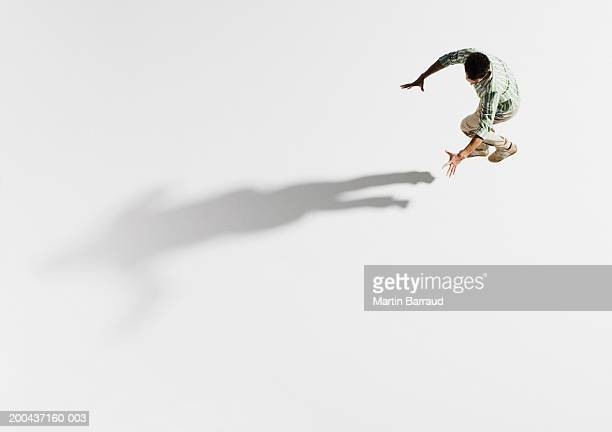 Young man jumping, holding arms out towards shadow, overhead view