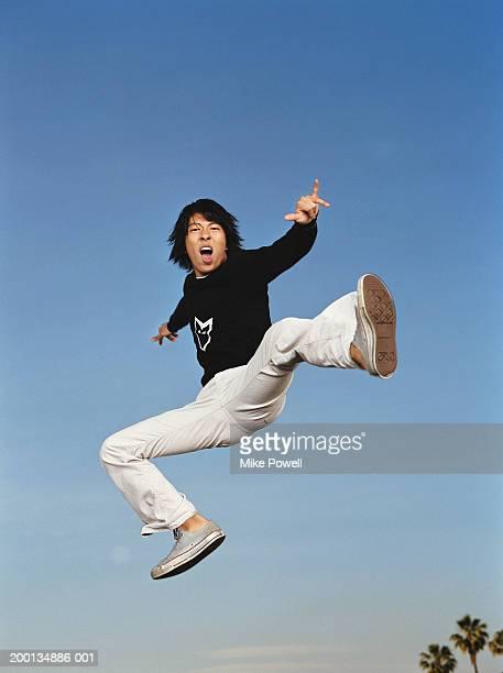 Young man jumping in air, kicking, Porträt, Flachwinkelansicht