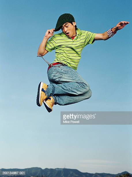 Young man jumping in air, portrait, low angle