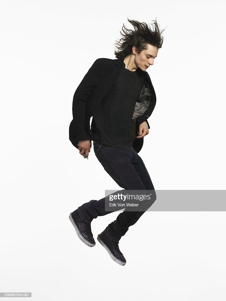 Young man jumping in air, side view : Stock Photo