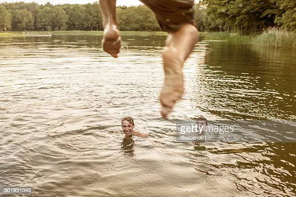 Young man jumping in quarry pond
