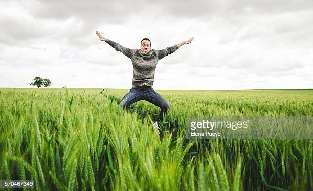 Young man jumping in wheat field