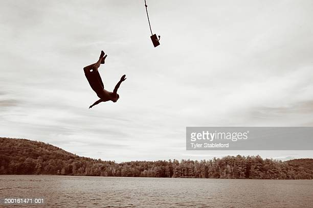 Young man jumping into lake from rope swing (Digital enhancement)